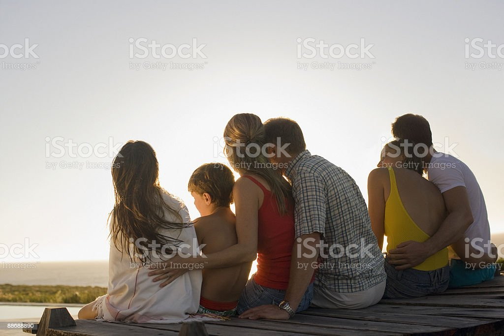 Family sitting on pier together royalty-free stock photo