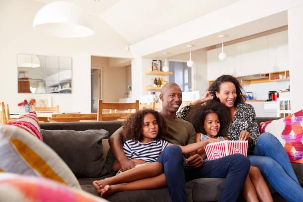 familia sentada en el sofá en casa comiendo palomitas de maíz y viendo películas juntos - family watching tv fotografías e imágenes de stock