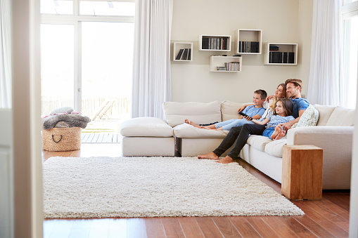istock Family Sitting On Sofa At Home Watching TV Together 937278694