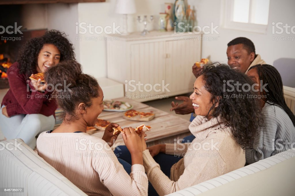 Family Sitting On Sofa In Lounge Next To Open Fire Eating Pizza stock photo