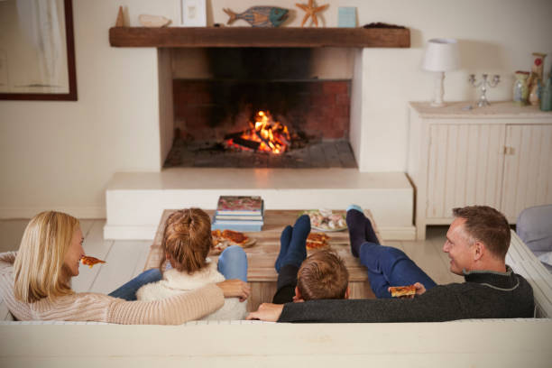 Family Sitting On Sofa In Lounge Next To Open Fire Family Sitting On Sofa In Lounge Next To Open Fire log fire stock pictures, royalty-free photos & images
