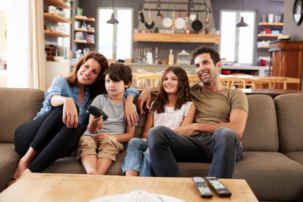 Família sentada no sofá, no salão de plano aberto, assistindo televisão - foto de acervo