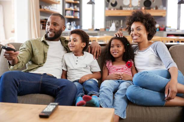 Famille assis sur le canapé dans le salon ouvert, regarder la télévision - Photo