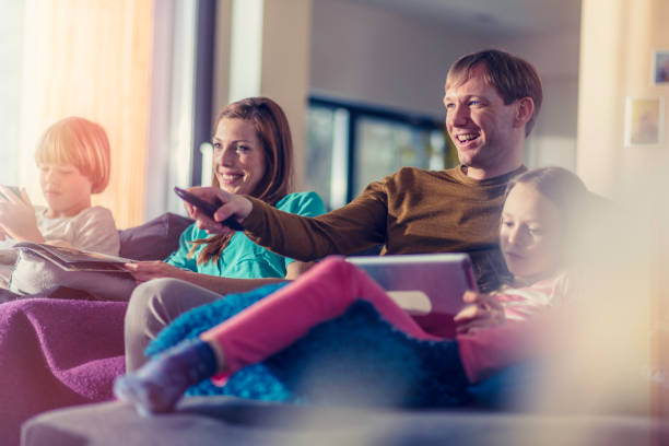 family sitting on sofa - family watching tv stock photos and pictures