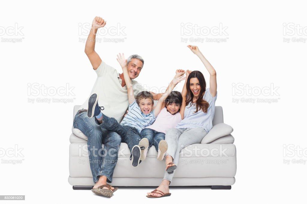 Family sitting on sofa raising their arms stock photo