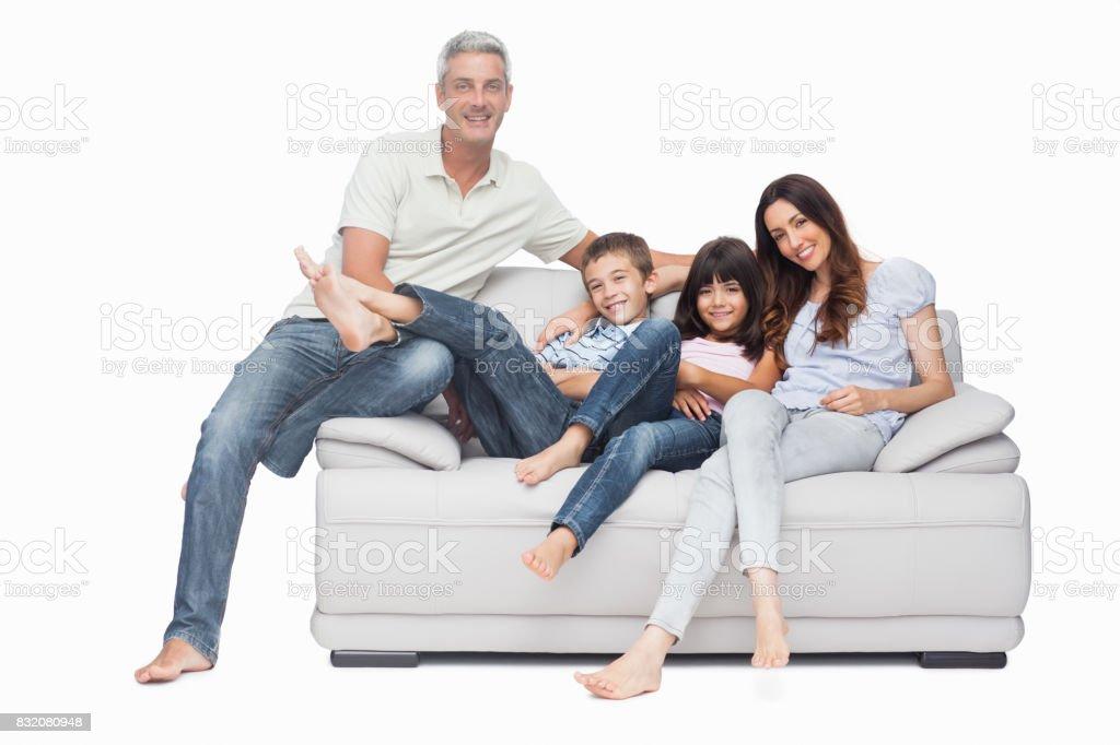 Family sitting on sofa smiling at camera stock photo