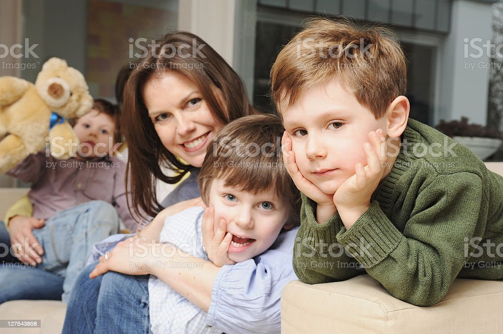 Family sitting on sofa together stock photo
