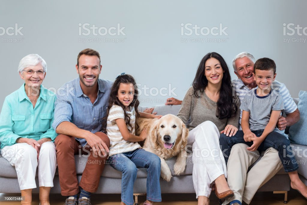 Family sitting on sofa with dog stock photo