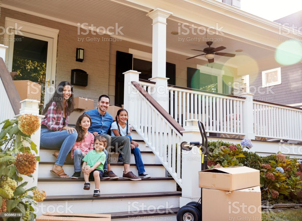 Family Sitting On Steps Of New Home On Moving In Day stock photo