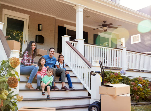 family sitting on steps of new home on moving in day - house hunting stock photos and pictures