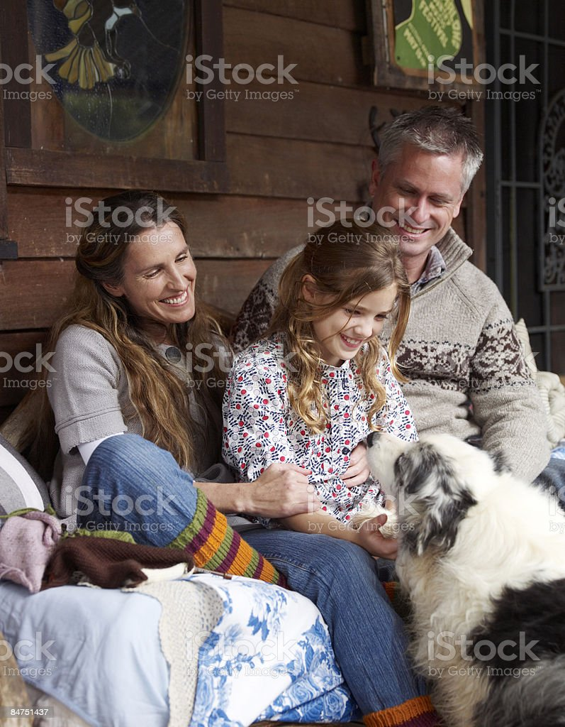 Family sitting on the porch of their country house royalty-free stock photo