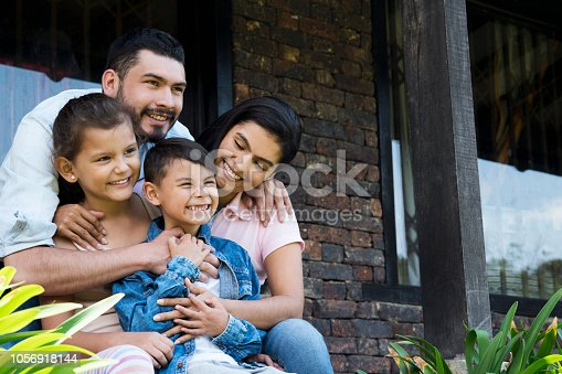 Beautiful family, sitting outside their country house, enjoying a beautiful day, smiling looking straight ahead, while the boy has his arm stretched