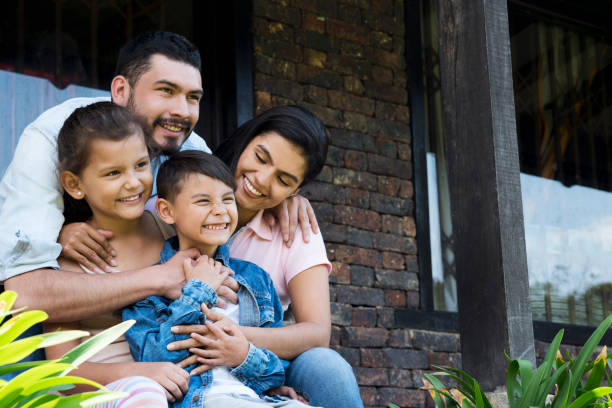 Family sitting outside their house Beautiful family, sitting outside their country house, enjoying a beautiful day, smiling looking straight ahead, while the boy has his arm stretched latin american and hispanic ethnicity stock pictures, royalty-free photos & images