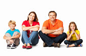 Portrait of a happy family sitting together with crossed legs. Horizontal Shot. Isolated on white.