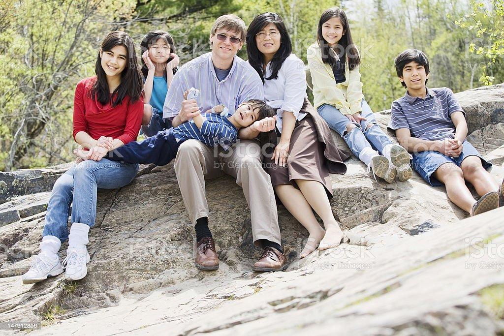 Family sitting together on rocky ledge stock photo