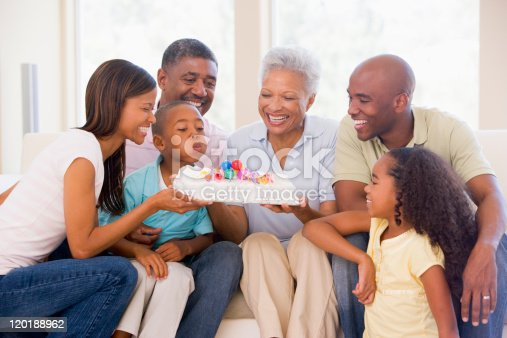 istock Family sitting with young boy blowing out candles on cake 120188962