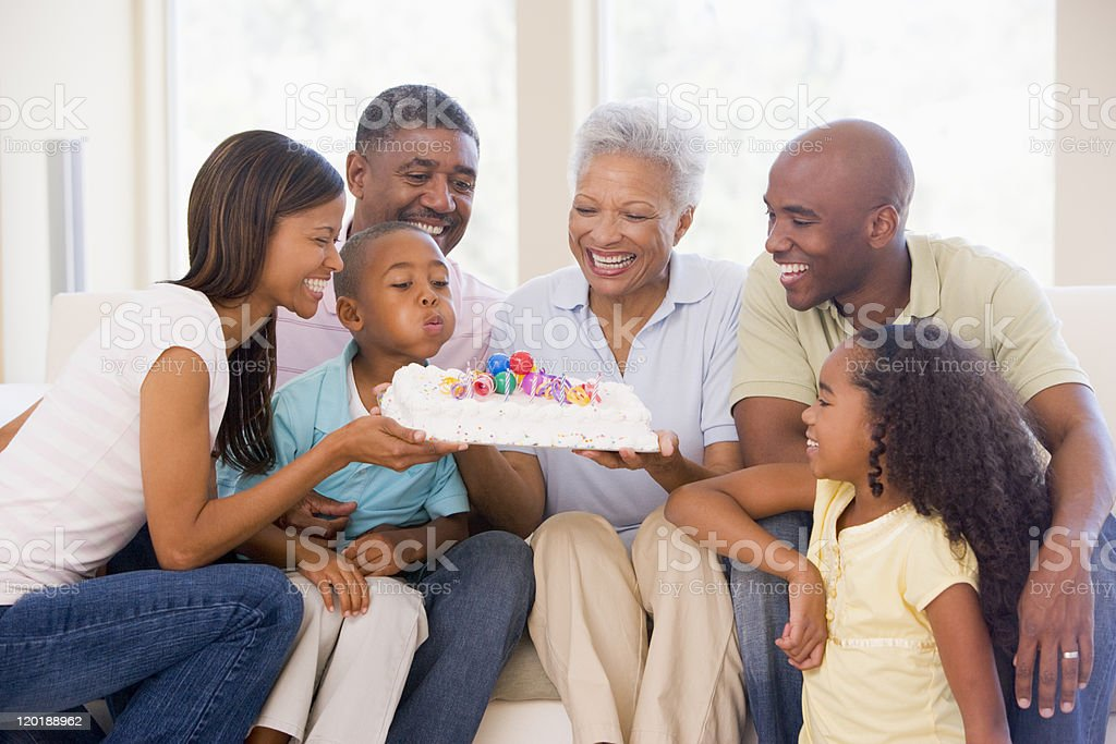 Family sitting with young boy blowing out candles on cake stock photo