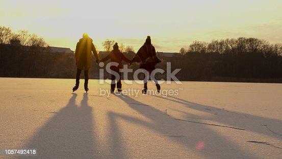 Family skating on frozen lake on sunset