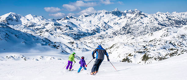 Family skiing Back view of a family with one child on ski slope. ski stock pictures, royalty-free photos & images