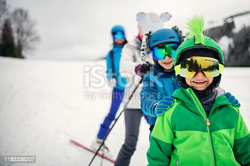 Mother with kids are enjoying skiing on a winter day. Sunny winter day. Nikon D850