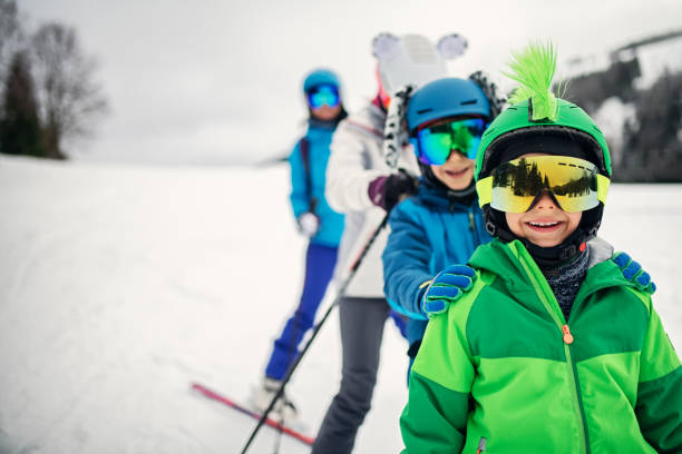 Family skiing together on winter day Mother with kids are enjoying skiing on a winter day. Sunny winter day. Nikon D850 ski holiday stock pictures, royalty-free photos & images