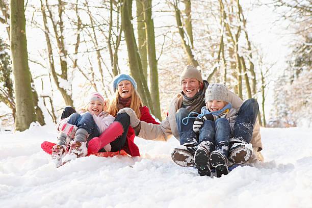 family sledging through snowy woodland - bos spelen stockfoto's en -beelden