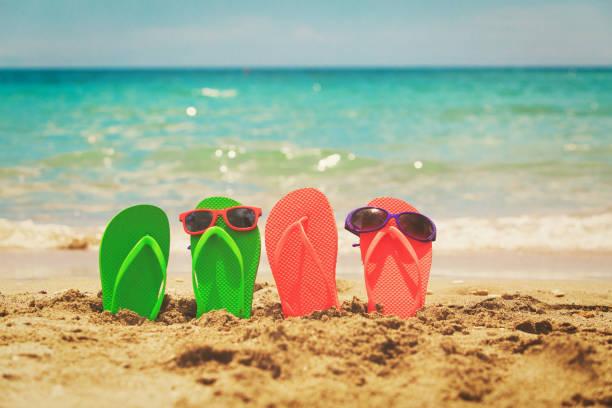 family slippers and sunglasses at beach - flitterwochen flip flops stock-fotos und bilder