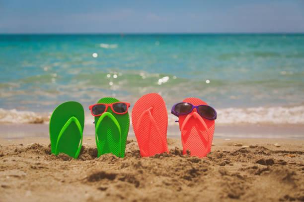 familie hausschuhe und sonnenbrille am strand - flitterwochen flip flops stock-fotos und bilder