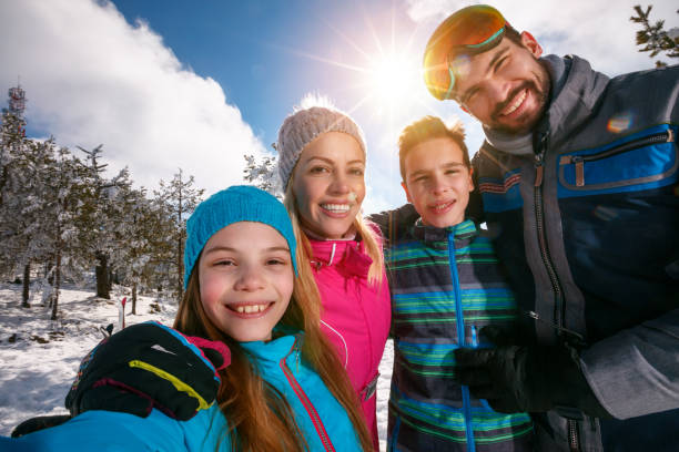 family smiling and making selfie on winter ski vacation stock photo