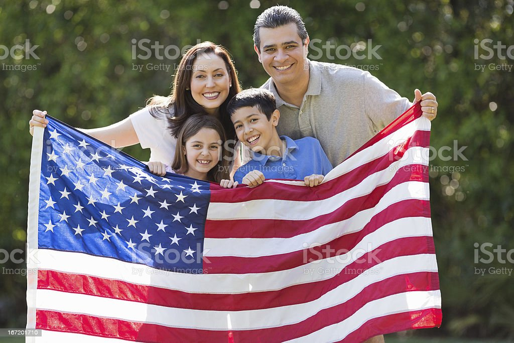 Family Smiling While Holding American Flag At Park stock photo