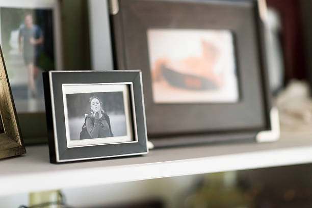 familie schnappschüsse gerahmte auf regal - katzenschrank stock-fotos und bilder