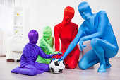 Colorful family in zentai suits joining hands on a soccer ball. Family is presented in different colors as unrecognizable people due to stop racism concept in mind. Idea in this series of photo was to simply show people as people without characteristics they can be defended as good or bad, black or yellow or white … So STOP RACISM
