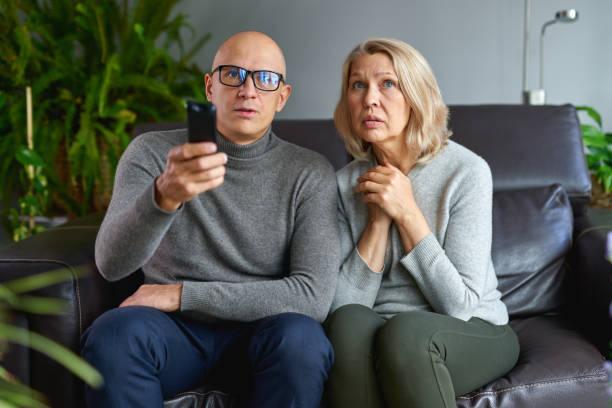 Hijo de familia y madre viendo la televisión juntos en casa. - foto de stock