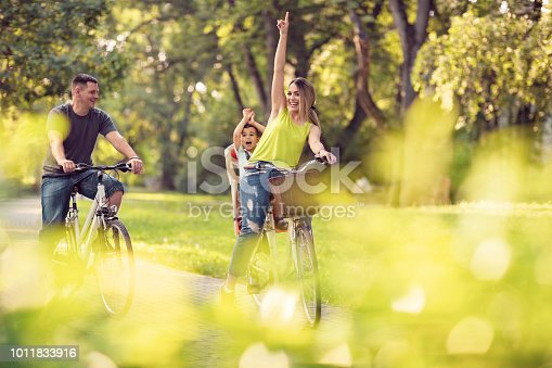 istock Family sport and healthy lifestyle. Happy father and mother with kid on bicycles having fun in park. 1011833916