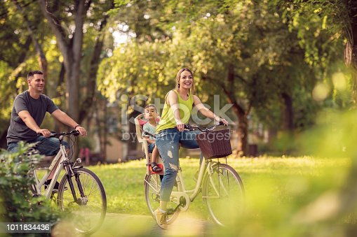 istock Family sport and healthy lifestyle. Happy father and mother with kid on bicycles having fun in park. 1011834436
