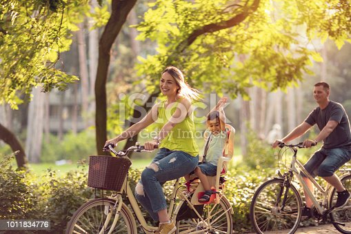 istock Family sport and healthy lifestyle. Happy father and mother with kid on bicycles having fun in park. 1011834776