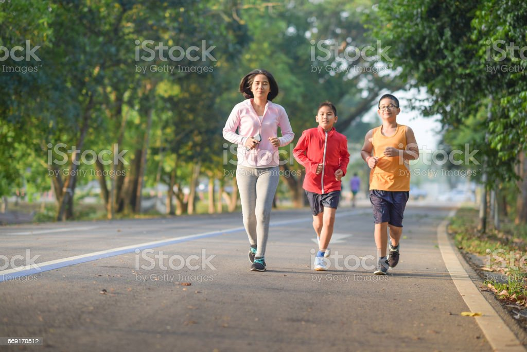 Family sport happy active mother and kids jogging outdoors running in forest stock photo