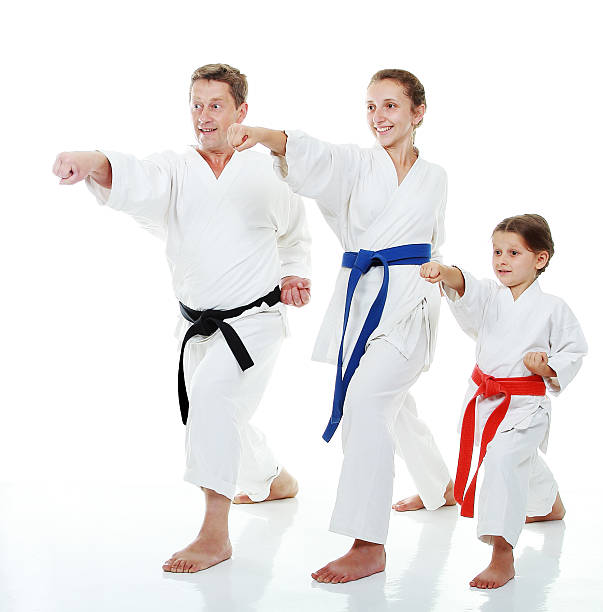 family sportsmen in a kimono beat punch arm - martial arts stock photos and pictures