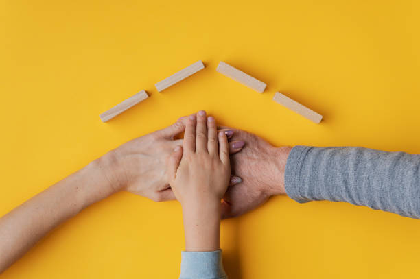 Family stacking their hand on yellow background with roof made of wooden blocks above their hands stock photo