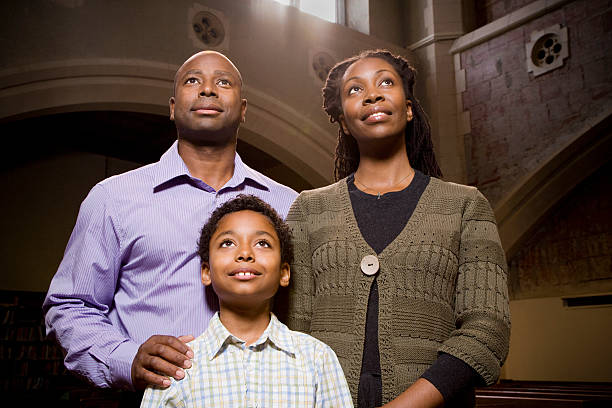 Family Standing and Praying in Church stock photo