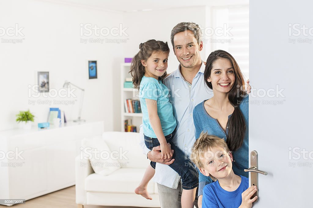 Family standing at front door to invite people home stock photo