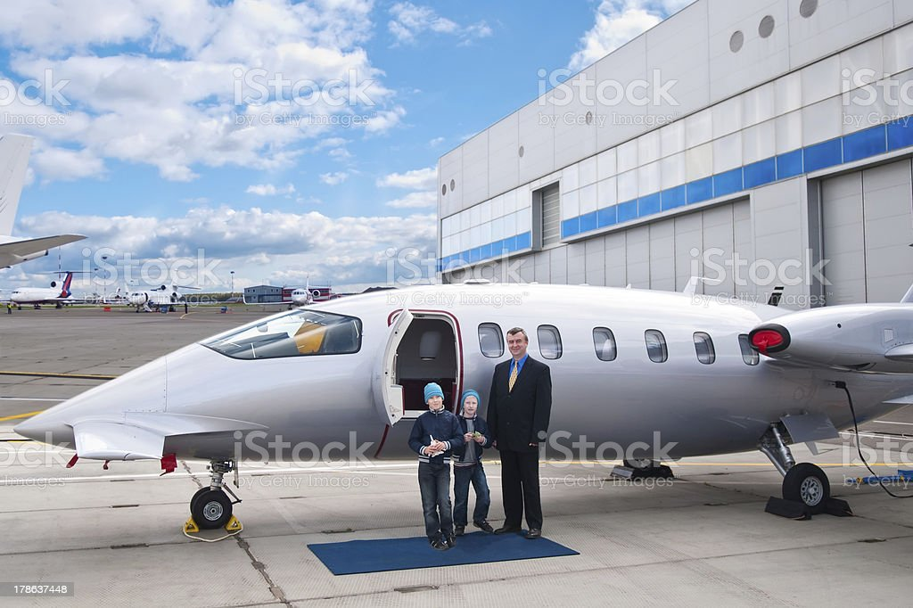 Family standing by business jet royalty-free stock photo