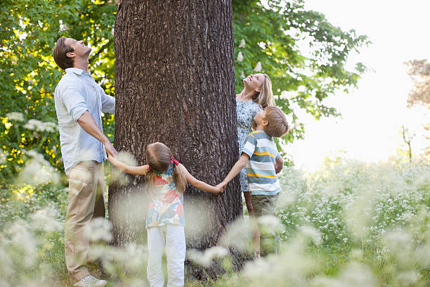 Family standing in circle around tree  tree hugging stock pictures, royalty-free photos & images