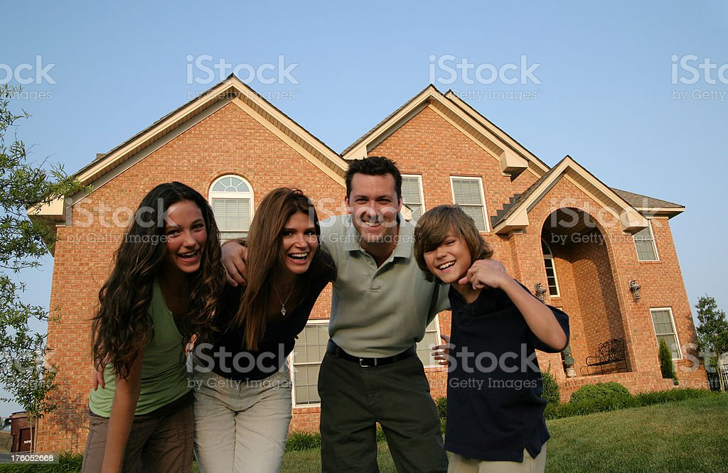 Family Standing in front of a house royalty-free stock photo