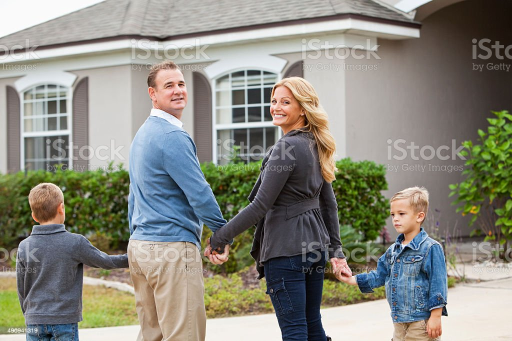 Family standing in front of house holding hands stock photo