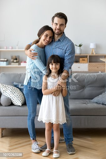 istock Family standing in living room embracing looking at camera 1070262038