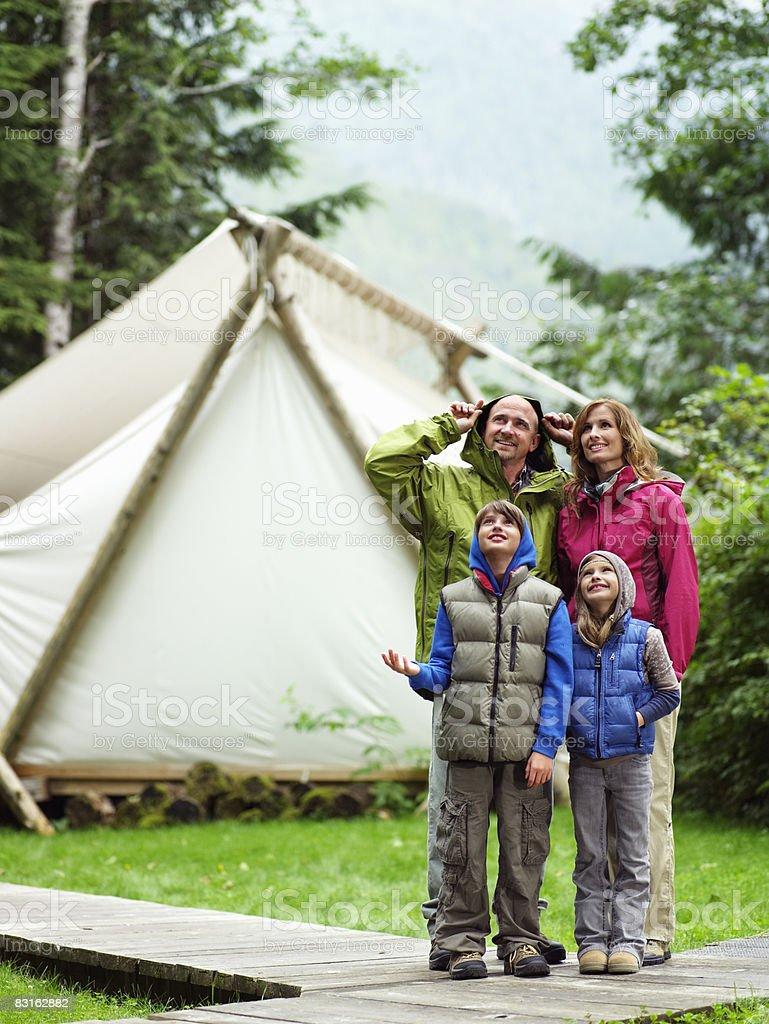 Famille debout sous la pluie en dehors de la tente. photo libre de droits