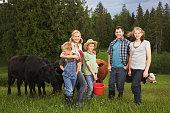 Family standing near cattle on farm