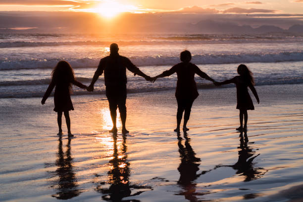 Family standing on beach at sunset silhouettes stock photo