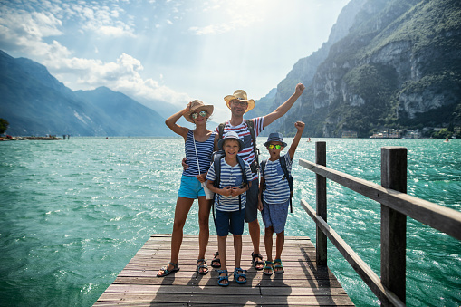 Family enjoying vacations in Italy. Father and kids are standing on a pier in Riva del Garda and cheering to the camera. Behind them there is magnificent view of Lake Garda surrounded by the Alps. Nikon D850